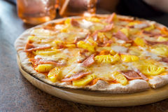 Ham and pineapple pizza. On wooden table with Spoon and Fork Tied Royalty Free Stock Photo