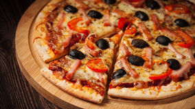 Ham pizza close up letterbox. Letterbox panorama of sliced ham pizza with capsicum and olives on wooden board on table Stock Photography