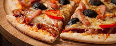 Ham pizza close up letterbox. Letterbox panorama of sliced ham pizza with capsicum and olives on wooden board on table Royalty Free Stock Image