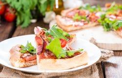 Ham Pizza con il razzo ed i pomodori freschi Immagini Stock