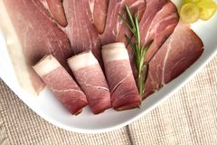 Ham plate. Delicious ham plate with grapes and rosemary stock photography