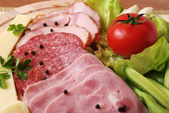 Ham platter with vegetables. Traditional ham and salami platter with vegetables royalty free stock photography