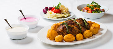 Ham, Potatoes and Salad. Meal of baked ham, oven roasted potatoes, salad, vegetables and sauces stock images