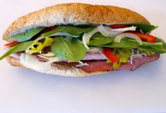 Ham and Roast Beef Sandwich -- a delicious sandwich for lunch. A ham and roast beef sandwich with jalapeno peppers, onions, parmesan cheese, spinach, and more Royalty Free Stock Photography
