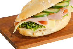 Ham roll. Baguette roll with ham, cheese, lettuce and cucumber slices on a wooden board royalty free stock images