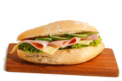 Ham roll. Baguette roll with ham, cheese, lettuce and cucumber slices on a wooden board, isolated royalty free stock photos