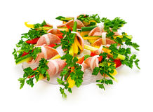Ham roll with fresh vegetables and parsley. Ham roll with fresh vegetables and parsley on a white background. Isolated Royalty Free Stock Images