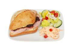 Ham roll and salad. Ham and pickle sourdough roll with salad and coleslaw on a plate isolated against white Stock Photography