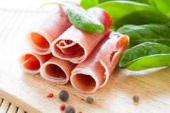 Ham rolled into a tube and green spinach Stock Images