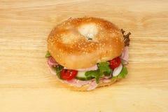 Ham salad bagel on a board. Ham salad bagel on a wooden chopping board stock photos