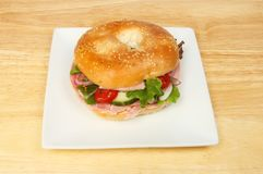 Ham salad bagel. On a plate on a wooden tabletop royalty free stock images