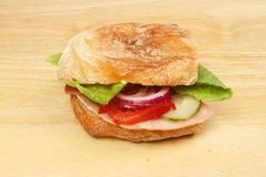 Ham salad ciabatta. Ham and salad in a ciabatta roll on a wooden chopping board stock images