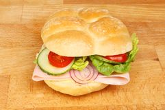 Ham roll on a board. Ham and salad in a plaited bread roll on a wooden chopping board Royalty Free Stock Photos