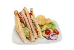 Ham salad sandwich. Made from lightly toasted bread with salad garnish and potato crisps on a plate isolated against white Stock Photo