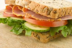 Ham salad sandwich. With cucumber, tomato and lettuce on wooden board Royalty Free Stock Photo