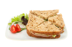 Ham salad sandwich with garnish. Ham salad sandwich made with wholemeal bread with salad garnish on a plate isolated against white Stock Photo