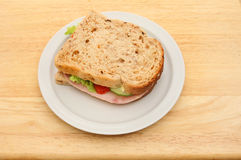 Ham salad sandwich. Ham and salad sandwich made with granary bread on a plate on a wooden tabletop Stock Images