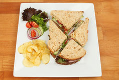 Ham salad sandwich on a table. Ham salad sandwich with salad garnish and potato crisps on a plate on a wooden tabletop Stock Photography