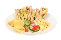 Ham salad sandwiches. With potato crisps, salad garnish and coleslaw on a plate isolated against white stock photo