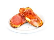 Ham and salami crostini. Isolated crostini with melted mozzarella cheese, serrano ham and turkey salami royalty free stock photo