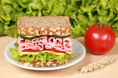 Ham Sandwich. Fresh sandwich with ham, cheese and lettuce on a wooden table royalty free stock photos