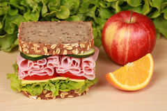 Ham Sandwich. Fresh sandwich with ham, cheese and lettuce, orange and aplle on a wooden table stock photography