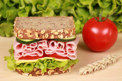 Ham Sandwich. Fresh sandwich with ham, cheese and lettuce on a wooden table royalty free stock image