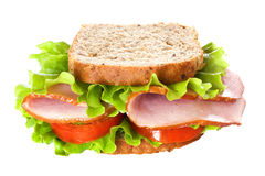 Ham sandwich closeup. Big healthy sandwich with wholewheat bread, ham, tomatoes and curly lettuce,  on white Royalty Free Stock Photos