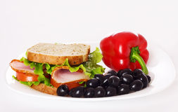 Ham sandwich closeup. Big healthy sandwich with wholewheat bread, ham, tomatoes and curly lettuce,  on white Stock Photo