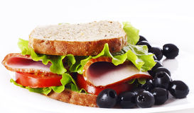 Ham sandwich closeup on the plate. Big healthy sandwich with wholewheat bread, ham, tomatoes, olive and curly lettuce on the plate Stock Photo