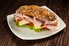 Ham sandwich. With lettuce, cheese, tomato on plate on wooden table Stock Image