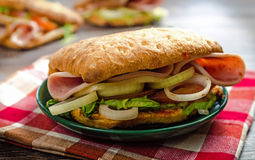Ham sandwich 2. Ham sandwich with onions and tomatoes on a wooden table Stock Image