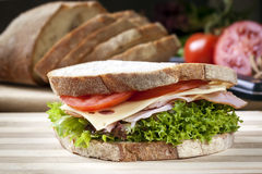 Ham Sandwich with Salad and Cheese. Loaf of bread behind Stock Photos