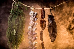 Ham, sausage and garlic in a homemade smokehouse Stock Images