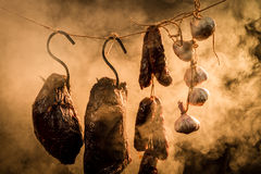 Ham, sausage and garlic in a smokehouse Stock Images