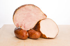 Ham and sausage on a wooden board Stock Photos