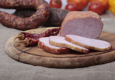 Ham sliced on a wooden board Stock Photos