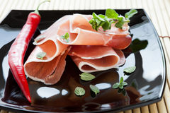 Ham slices on a black plate Stock Photography