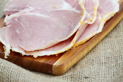 Ham slices wooden chopping board hessian A Royalty Free Stock Images