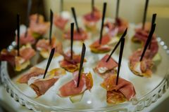 Ham snack on skewers on glass plateau. Ham snack on black skewers served on glass plateau in catering service royalty free stock photo