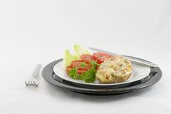 Ham & Swiss-Stuffed Potato. Light lunch or dinner consisting of a baked potato stuffed with ham, swiss cheese, and parsley. Served with sliced tomatoes on a bed royalty free stock images