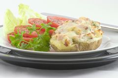 Ham & Swiss-Stuffed Potato. Light lunch or dinner consisting of a baked potato stuffed with ham, swiss cheese, and parsley. Served with sliced tomatoes on a bed Royalty Free Stock Photo