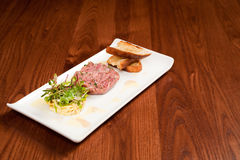 Ham Terrine with cabbage. Ham hock terrine with shredded cabbage and home made toasted bread on a white rectangular plate Royalty Free Stock Photos