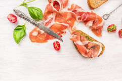Ham with toast,knife, Basil and pesto on white wooden background Stock Photo