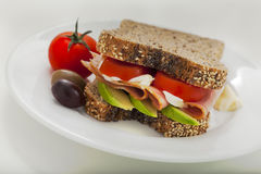 Ham, tomato and avocado sandwich. Delicious ham, tomato and avocado sandwich with wholemeal bread, mayonnaise and olives Stock Photography