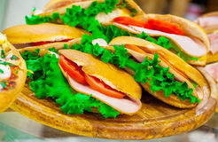 Ham, tomatoes sandwiches and lettuce leaves Stock Photo