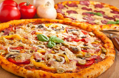 Ham and Veg Pizza with Salami Pizza at the Back Stock Photos