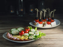 Ham with vegetables and quail eggs and Camembert canapes with cherry tomatoes and olives.  royalty free stock photos