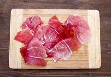 Ham on wooden cutting board on top. Ham on cutting board on wooden table seen from above Stock Photography
