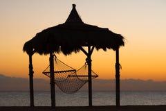 Hamac à la plage pendant le coucher du soleil Images libres de droits
